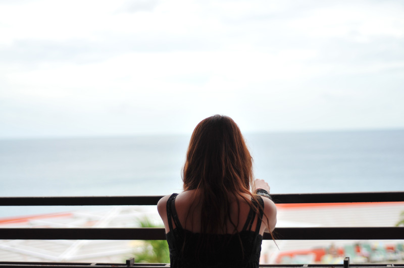 woman looking over balcony at ocean