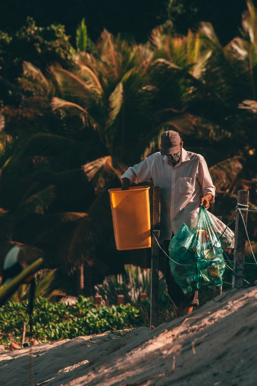 faceless black cleaner collecting garbage from street bin