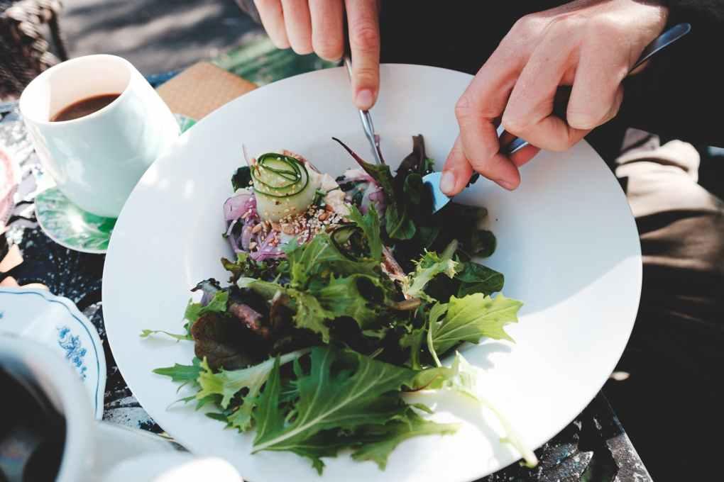 crop unrecognizable man eating fresh mix leaves salad