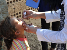 A health worker gives a child oral polio vaccine in Syria