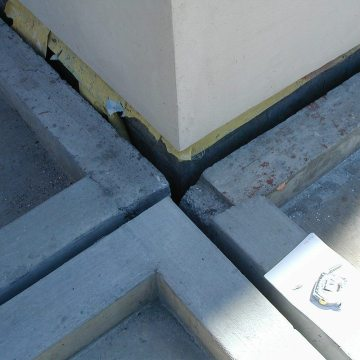 Perimeter expansion joints between the parking deck roof and each building intersect with mid-span structural joints at every building corner. The top deck is a hot-rubberized asphalt-waterproofed split-slab. Continuity of seal through changes in plane and direction, from deck-to-deck to deck-to-wall was a fundamental performance criteria.