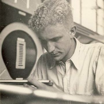 Peter Hensley working as aeronautical engineer using a slide rule to make measurements.