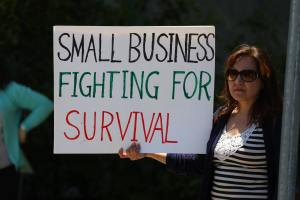 "A woman holding a sign ""Small businesses fighting for survival"""