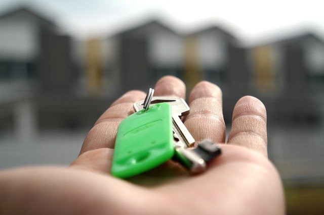 A man holding home keys on an open palm ends the Mississippi home buying process.