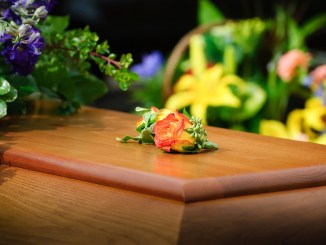 Photo of casket surrounded by flowers