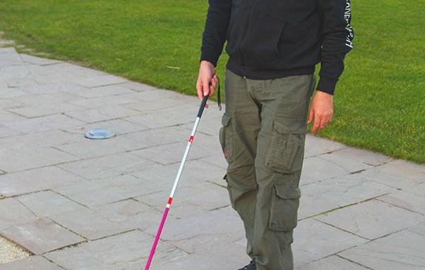 Photo of a man using a folding white cane