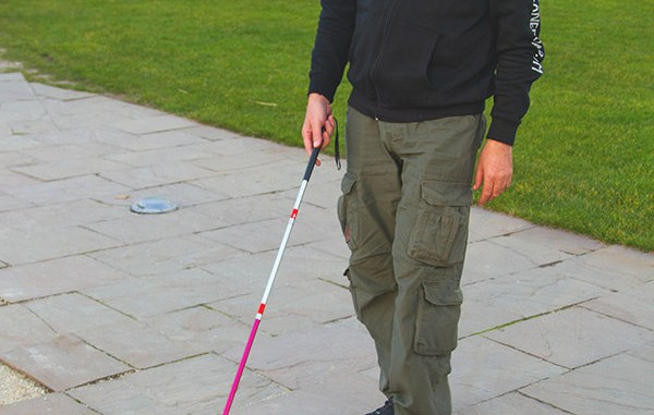 Photo of a man using a folding white cane