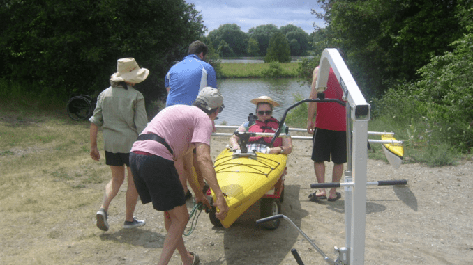 Connie in a yellow kayak being assisted into the water by four people