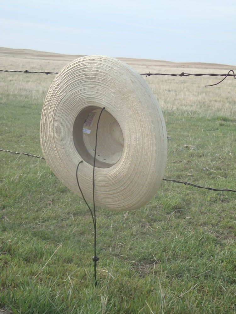 A barbed wire fence held my  Sunbody hat long enough for me to retrieve it.
