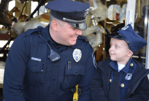 endicott police officer smiling with toddler 1 - endicott-police-officer-smiling-with-toddler
