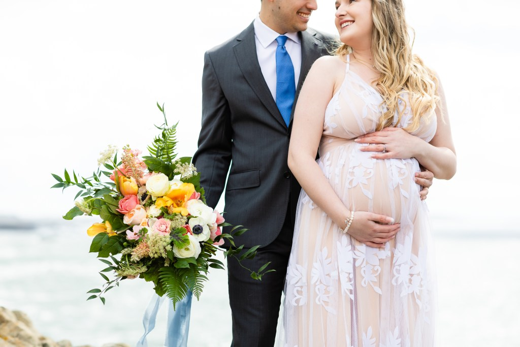 Shannon and Daniel smile at eachother. Shannon holds her belly and Dani touches it with one hand and holds flowers in the other.
