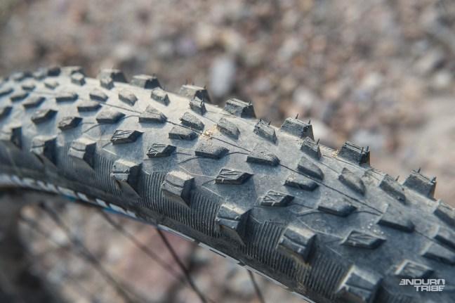 La gomme utilisée est aussi une dérivée de ce qui compose la gamme Enduro : la Gum-X3D partage en partie les composants de la Gum-X d'Enduro, la plus dure, susceptible d'apporter le rendement et la durabilité exigée. 3D pour marquer le nombre de gommes différentes : les nappes de la carcasses liées par la sous-couche qui assure l'intégrité du pneu, une couche externe qui joue le compromis grip/rendement, et les crampons latéraux dans une version plus accrocheuseencore.