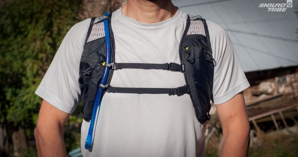 Ici pas de ceinture ventrale pour le maintien du sac. Seul une sangle et un élastique, ajustable en hauteur, assurent la fermeture sur le torse. L'ergonomie du sac sur le dos étant bonne, c'est amplement suffisant ainsi. Le sac n'a pas tendance à bouger ou à remonter dans le cou lors d'un saut ou dans la pente. Le tuyau est clipsé à deux endroits. Qui sont eux aussi ajustables. A savoir que si le clip du bas est vraiment bas, il est nécessaire de le éclipser pour boire en roulant : sinon, le tuyau se plie et l'eau ne circule pas.