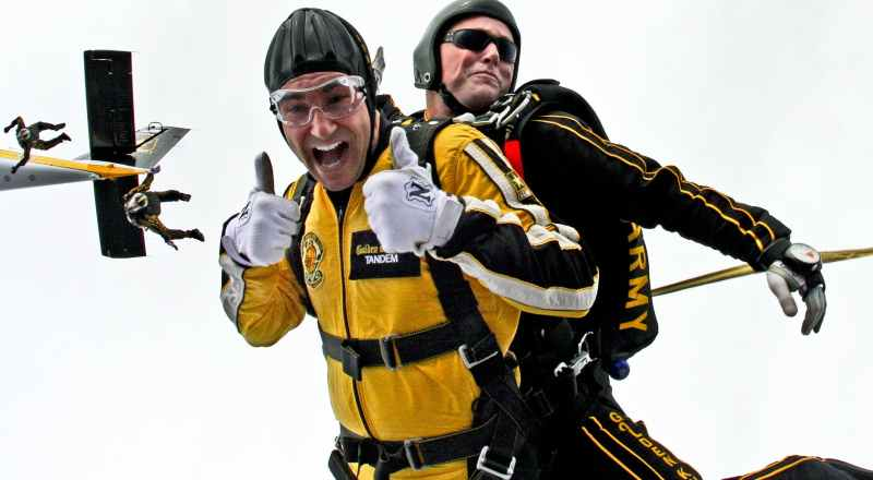 parachuter in yellow suit doing a thumbs up