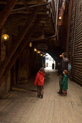 touristes-dans-ruelle-entre-maison-de-quai-bryggen-classé-à-Unesco-Bergen-Norvège