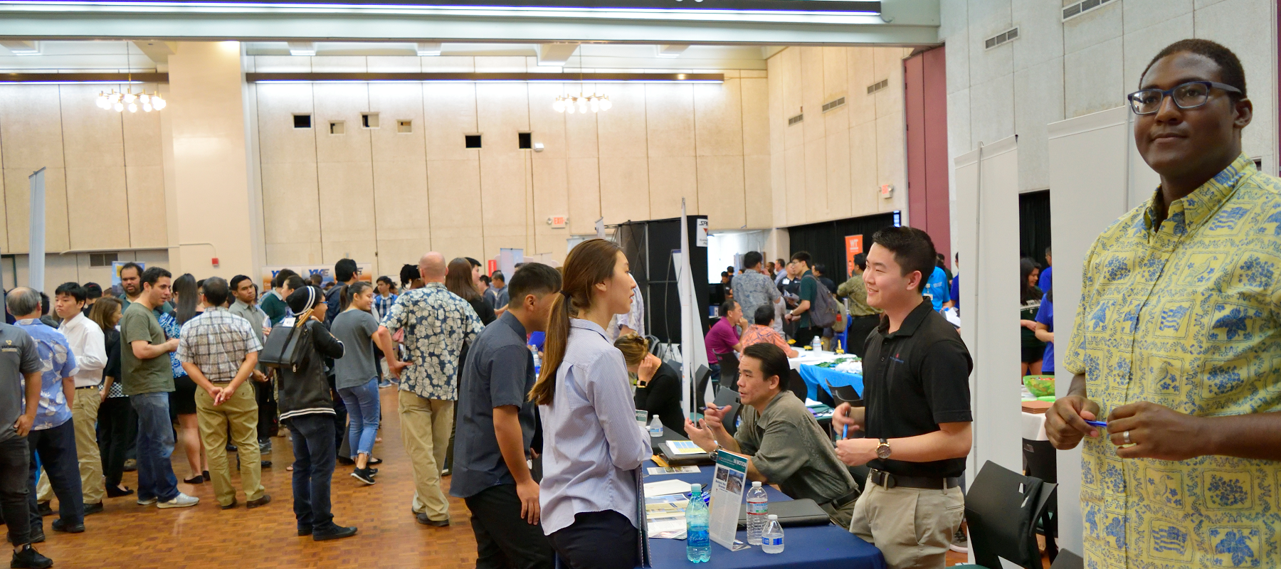 A Wide-shot Of Students And Employers Interacting At Career Day.