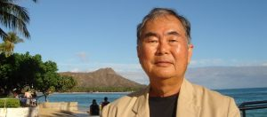 Headshot of Patrick Takahashi with Diamond Head in the background.