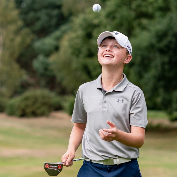 Young boy throwing catching a golf ball