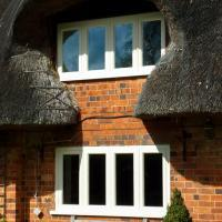 bespoke windows fitted in period red brick thatched cottage by james pillier joinery