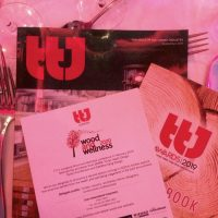 TTJ Awards dinner setting with journal and wood and wellness info