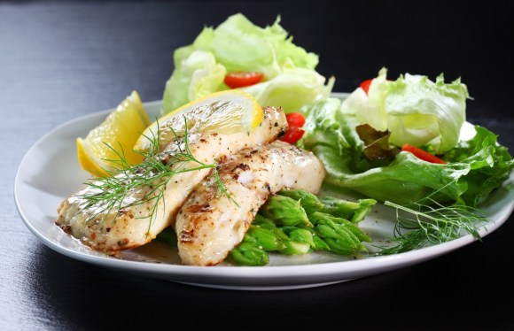Fish on green asparagus with salad