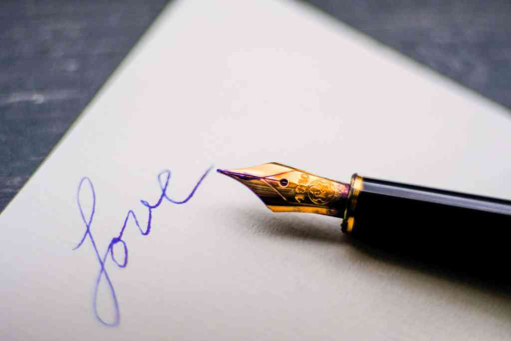A fountain pen writes the word love on paper