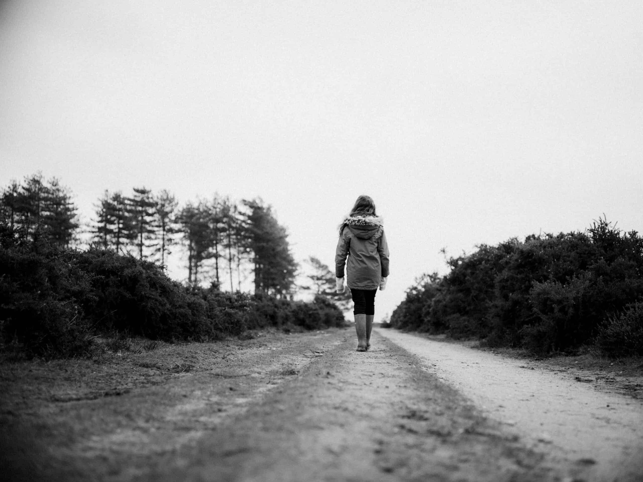 a black and white photo of a woman walking down a wide pathway