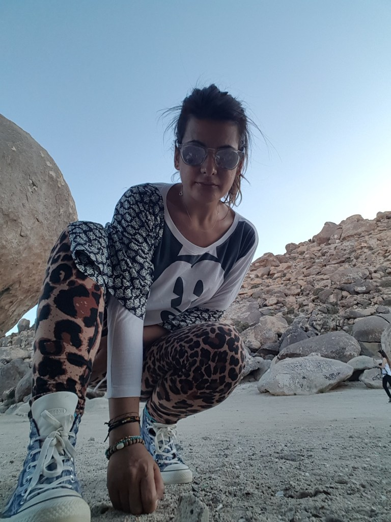 girl dressed in sporty clothes in a rocky desert