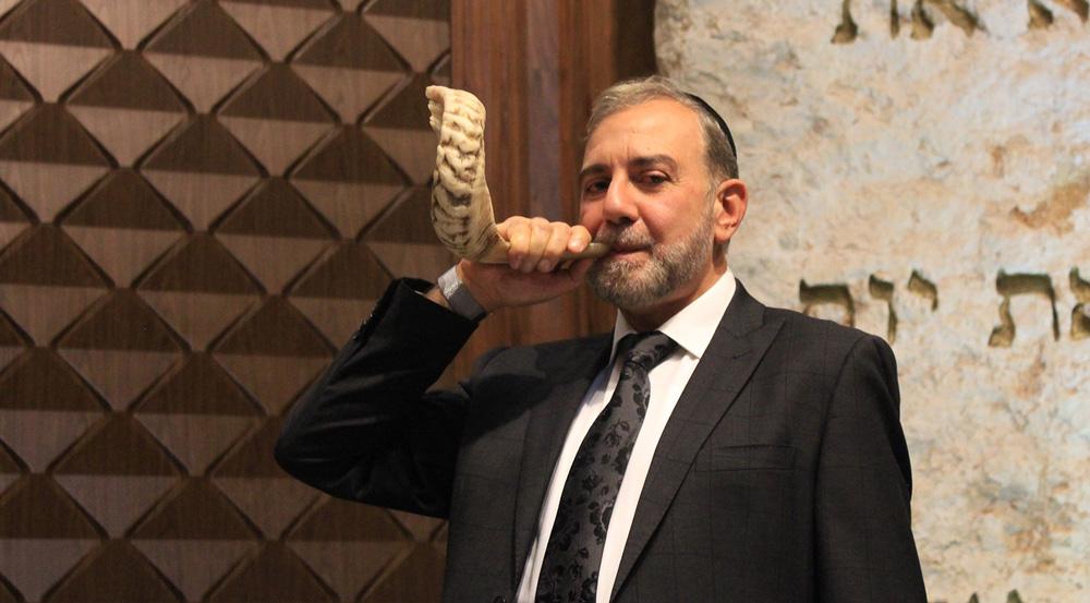 rabino tocando el Shofar en la sucá