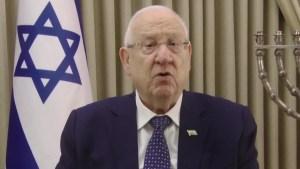 Reuven rivlin habla frente a la cámara en la Residencia del Presidente de Israel con la bandera nacional y la menorá