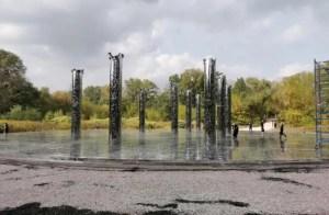 Monumento conmemorativo en medio de un bosque, sobre una amplia explanada, sobre una superficie redomda de espejo, y alta columnas negras como rotas arriba, 3 o 4 personas caminan entre ellas. El cielo está gris,