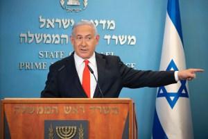 Netanyahu habla en rueda de prensa en la Knéset, estira su brazo izquierdo como señalando algo. A su izquierda, una bandera de Israel, detrás un cartel celesta con letras blancas en la pared indica que es la oficina del primer ministro del Estado de Israel. Delante suyo hay un atril de madera con la inscripción Oficina del Primer Ministro y una menorá como símbolo del estado. Netanyahu viste traje oscuro, camisa blanca y corbata roja.