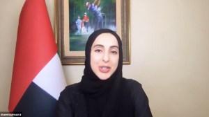 La joven ministra emiratí aparece sentada vstida de negro con la cabeza cubierta pero el rostro totalmente descubierto, detrás a su derehca tiene la bandera de emiratí y detrás suyo colgado en la pared un cuadro de un hombre vestido de azul jugando al golf y otros dos jugadores que se le acercan.
