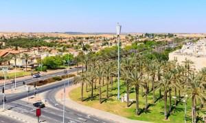 vista de una zona en crecimiento en medio del desierto, con vegetación incipiente y árboles nuevos destinada a urbanizar, a un lado de la calle se ven casa bajas blancas con tejados naranja, al otro los árboles. En un cruce de acimonos se ve un coche llegar