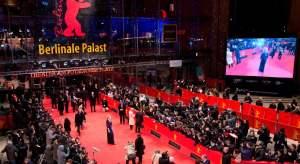 Entrada al Teatro de la Plaza Potsdam sede del Festival de cine de Berlín, un enorme cartel del festival con letras en dorado y el oso, logo del festival en rojo, con alfombra y separaciones en rojo, público a ambos lados del pasillo de entrada, donde posan artistas y directores.