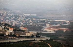 Paisaje campestre, en primer plano a la izquierda una población con casas blancas con tejados naranja se divisa con claridad, al fondo, la imagen es difusa, probablemente se trate de una población libanesa, una carretera serpentea en medio de la imagen y a la derecha plantaciones.