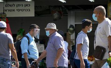 Personas con cubrebocas y caretas caminan por una calle de Israel