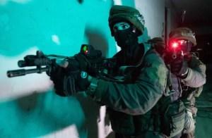 Un soldado con casco, guantes y la cara semicubierta apunta con un arma hacia adelante, detrás otro en idéntica posición y con el mismo aspecto apunta hacia la cámara, un flash se dispara, toda la imagen parece iluminada por infrarojos.