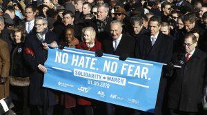 Cabeza de la marcha contra el antisemitismo en Nueva York con personalidades famosas sujetando un cartel celeste con letras blancas donde se lee No al odio, No al mmiedo. Por la ropa se observa que es invierno