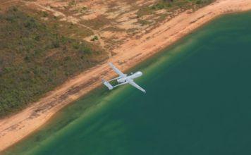 un dron gris sobrevuela la costa, el mar se ve verde y la tierra es desierta con poca vegetacion