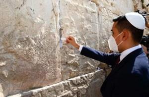 Un hombre con traje azul y camisa blanca, kipá y mascarilla contra el virus, deposita un papel en el Muro Occidental