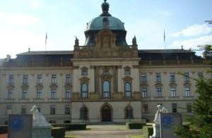 frente de un edificio de época de tres plantas, fachada beige, cúpula verde/celeste claro, visto desde la explanada de la entrada flanqueada a los lados por una estatua