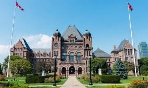 postal del Parlamento de Ontario visto de frente con zona ajardinada a los costados del camino que lleva a la entrada, sobre fomdo del cielo azul. Dos baneras canadienses a los costadosa la entrada de los jardines