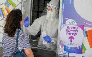 Laboratorista toma una muestra nasofaringea a una mujer para una prueba de coronavirus en Israel