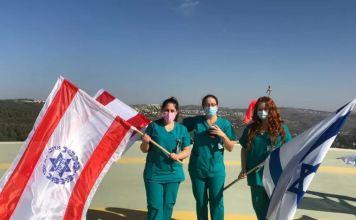 tres mujeres del personal sanitario vestidas con traje verde del hospital y mascarillas, sostienes banderas del Hospital y de Israel en la explanada del techo del centro médico