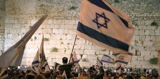 Multitud frente al Kotel con banderas de Israel