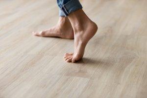 Acercamiento lateral pies de mujer sin zapatos en un cálido piso de madera