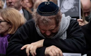 Judío con Kipá con la cabeza agachada sobre sus brazos cruzados