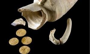jarro de arcilla recostado, con el borde superior roto y el trozo al costado, 4 monedas antiguas de oro delante, todo sobre fondo oscuro