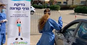 Laboratorista toma muestra nasofaringea a una persona en su auto para una prueba de detección de coronavirus en Israel